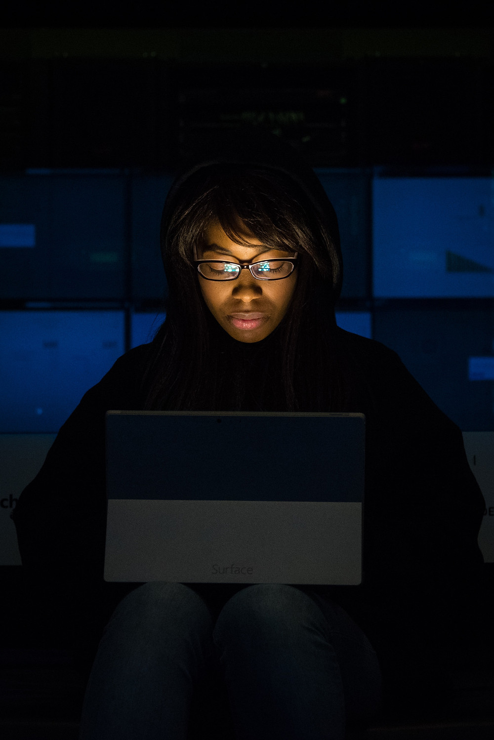 A person sits in the dark looking at their laptop, contemplating the future of work.