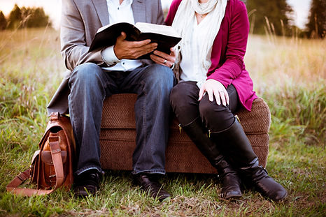 Man and woman in casual church attire sitting in a field looking through bible