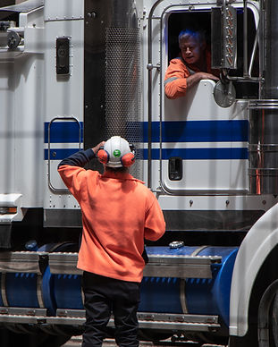A laborer speaks to a coworker on a truck.