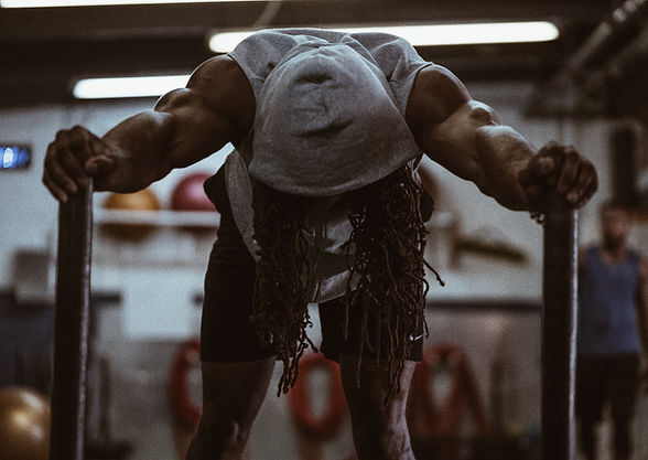 Black man with head down pushing weighted sled