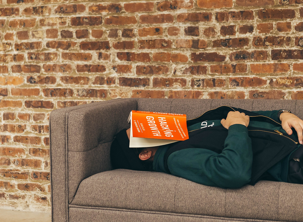 man sleeping on the sofa with an orange book on his face
