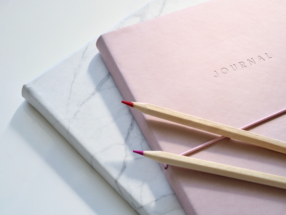 a stack of elegant, beautiful writing journals with colored pencils on top