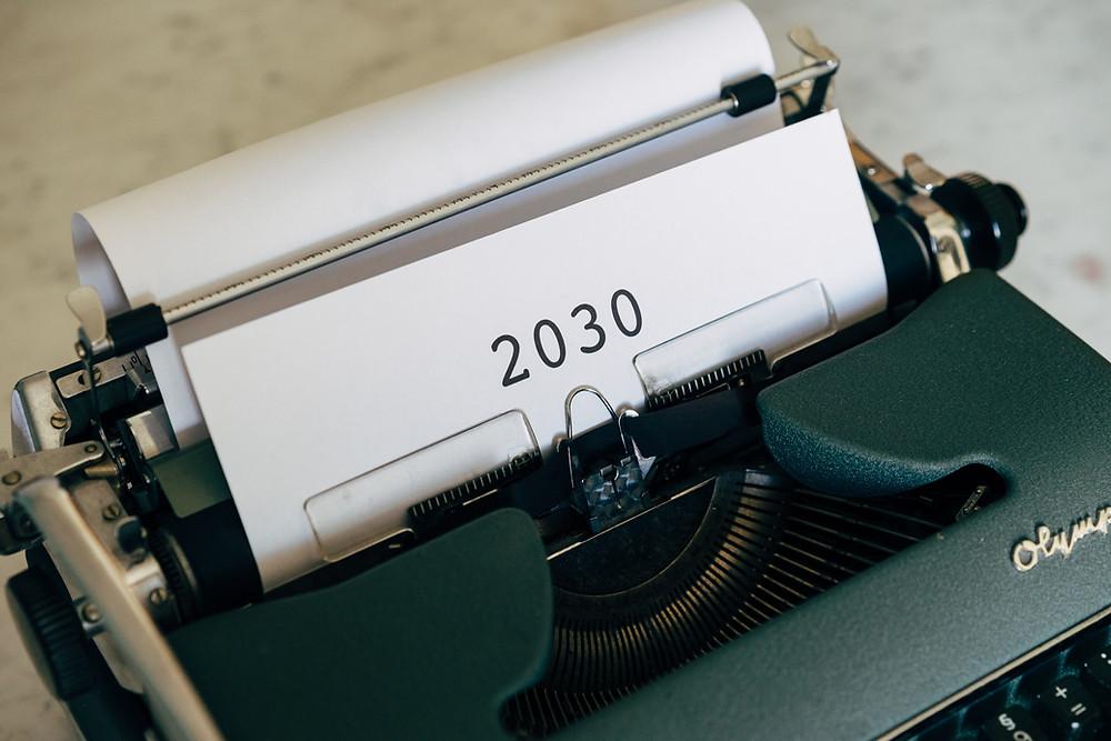 Schreibmaschine, in die ein Blatt mit der Aufschrift 2030 eingespannt ist.