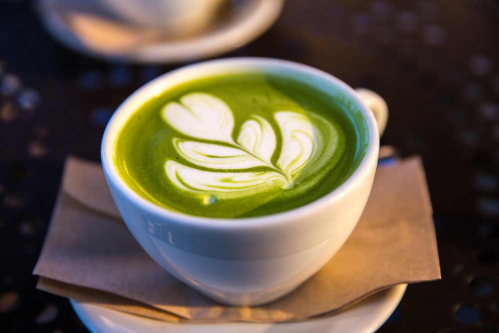 A cup of matcha latte with matcha latte art on top.