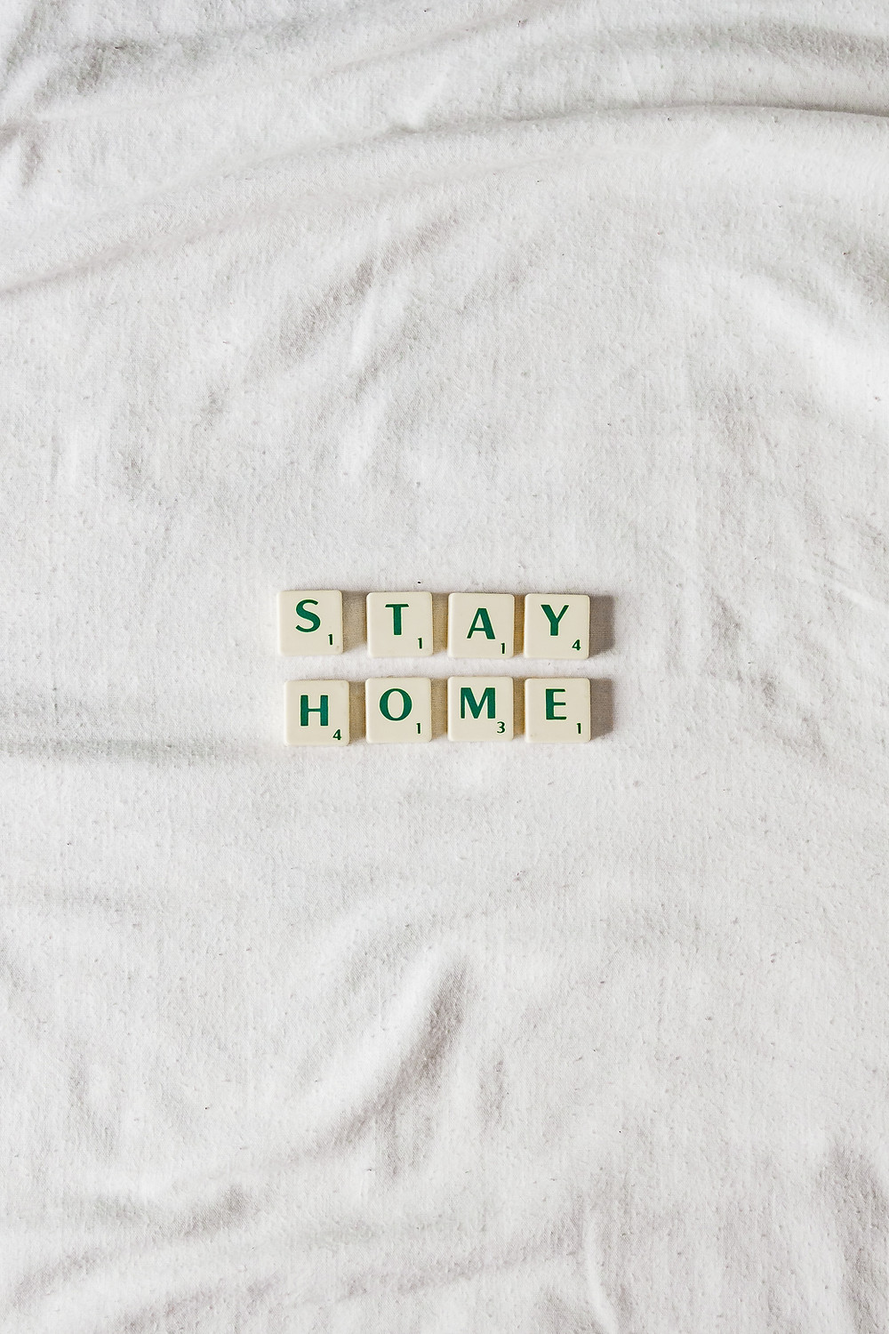 "Scrabble game tiles that spell out ""Stay Home."""