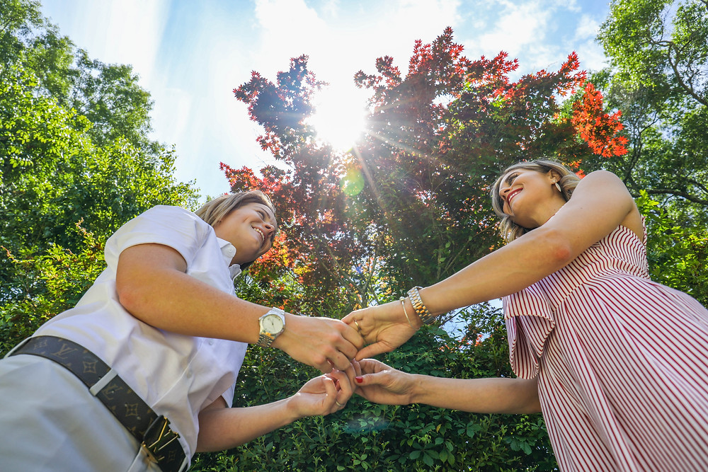 Lesbian couple holding hands with trees in the background