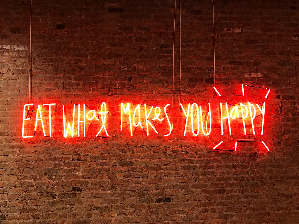 "Neon sign reading ""eat what makes you happy"""