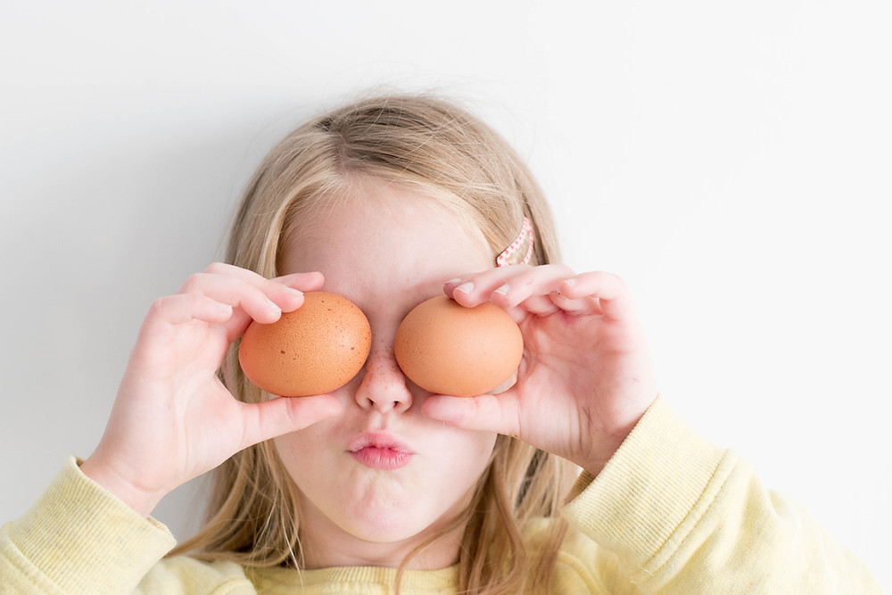 young girl holding 2 eggs to her eyes