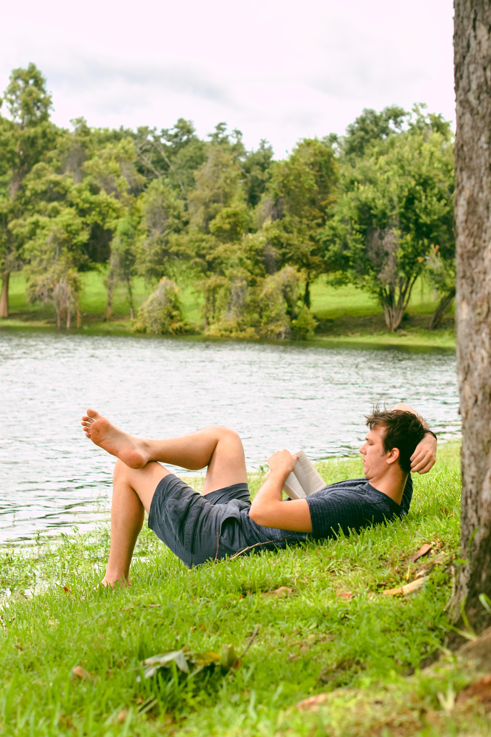 Caucasian man reading and lounging on the grass in a natural setting