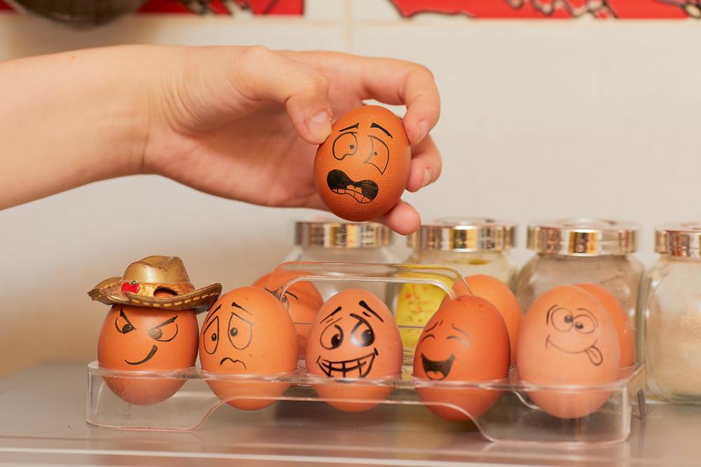 Uma mão levanta um ovo, tirando-o de uma prateleira com outros ovos com rostos pitandos.