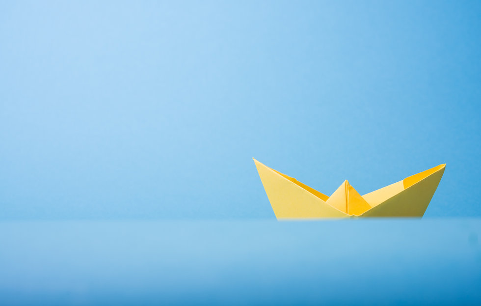 A photo of a yellow paper boat on a blue background.
