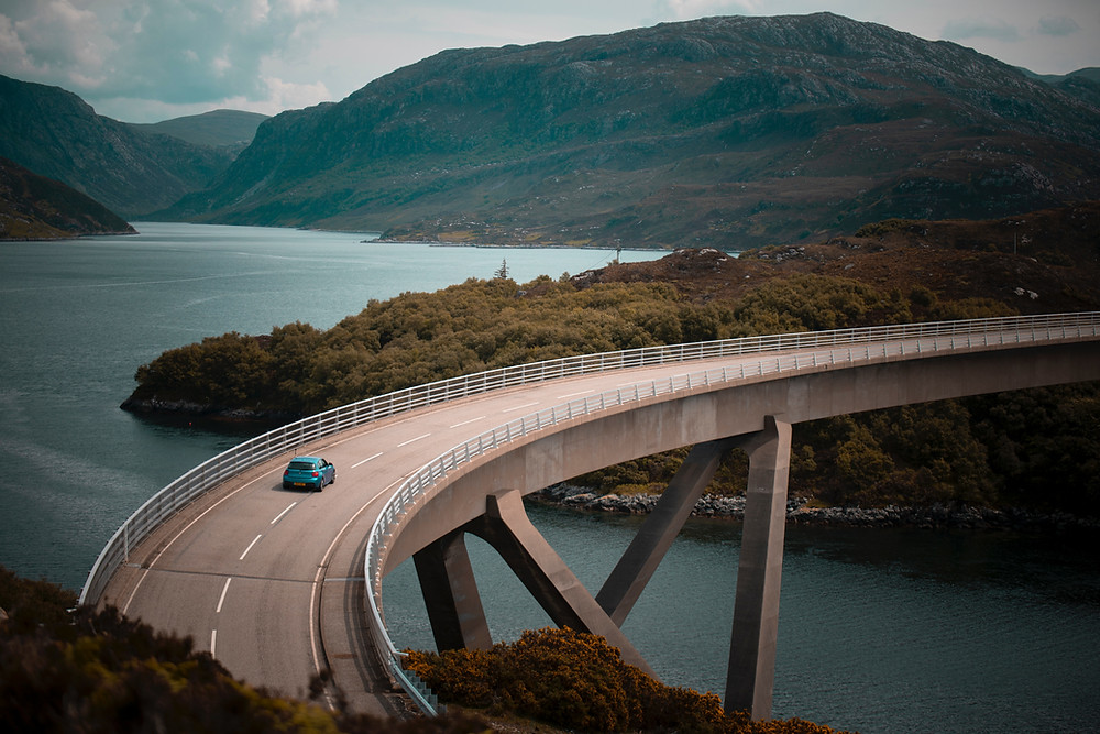 A car travels down a scenic road