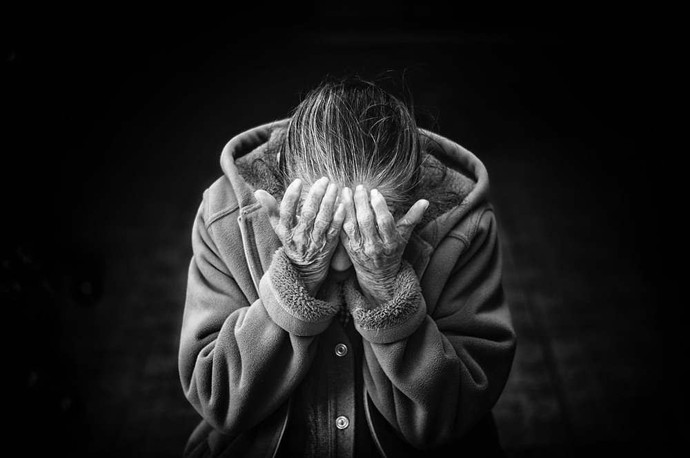 A person suffering from grief and loss with head in hands