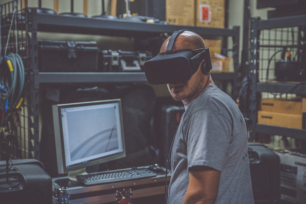 A man with a VR headset is turning around, away from a white monitor and a shelf with tools