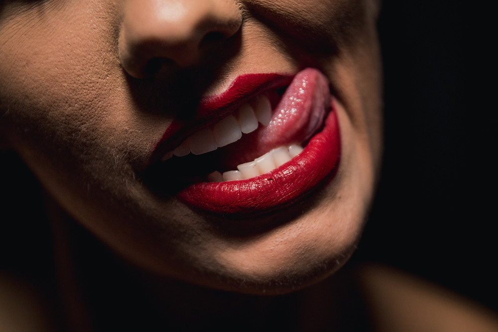 closeup of a woman's face white her tongue out wearing red lipstick