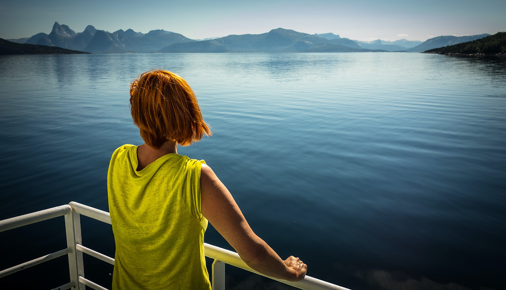 View from behind of woman with short red hair in lime t-shirt looking over lake and mountains