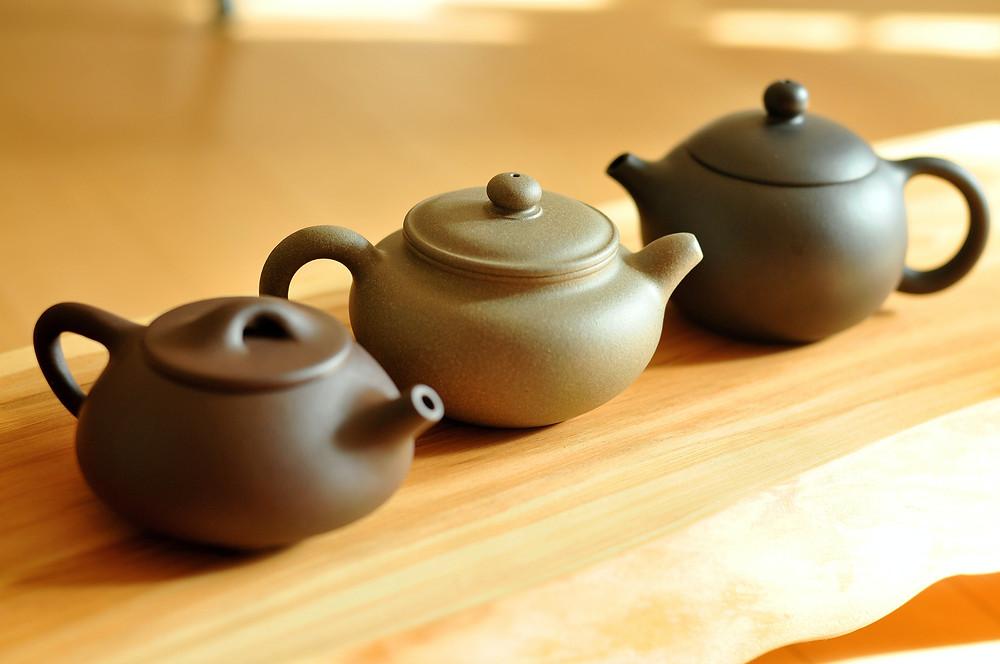 3 Teekannen stehen auf einem Holzbrett