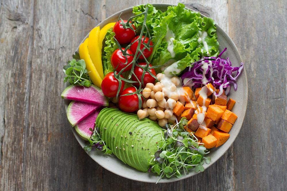 A bright bowl full of vegan food like avocado, tomatoes, potatoes, watermelon, lettuce, mango, chickpeas and mango.