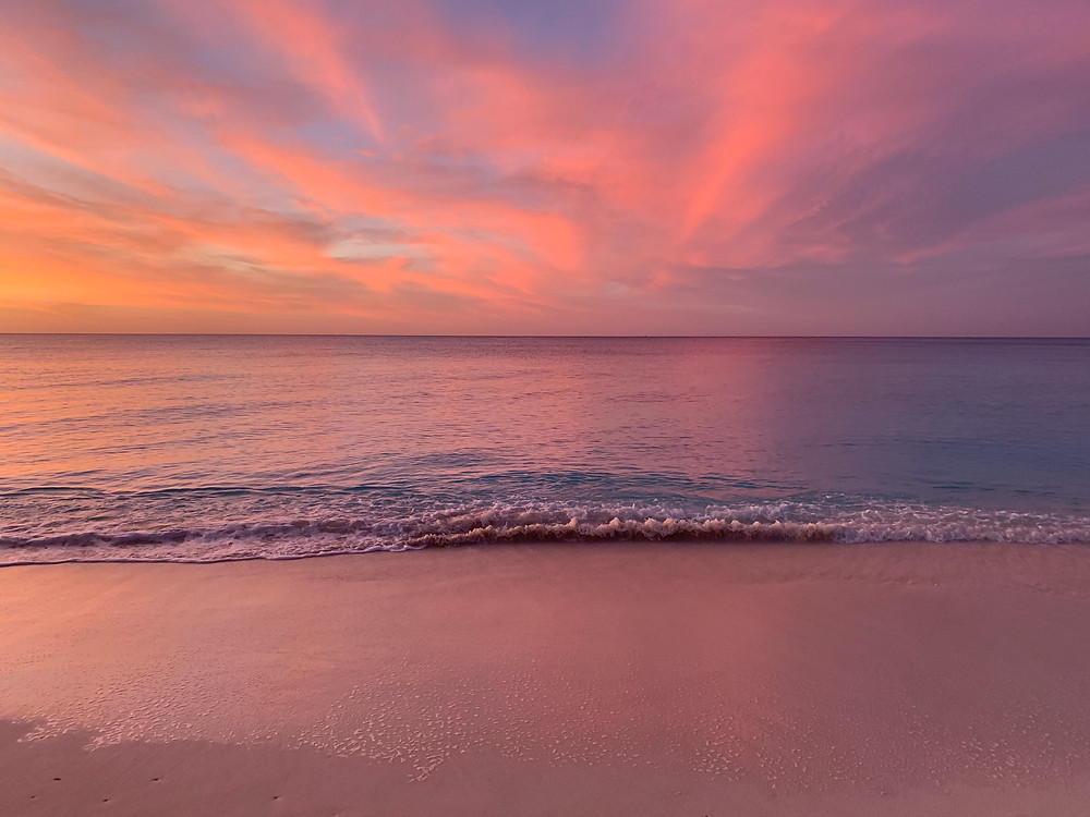 A sunset with cotton candy pink skies and a pink ocean.  The waves are gently crashing on the shore.