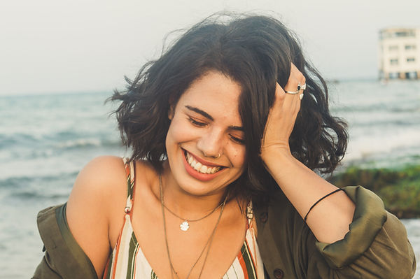 Image by Chermiti Mohamed - woman with short curled hair with her shirt coming off her shoulder laughing with her eyes closed.