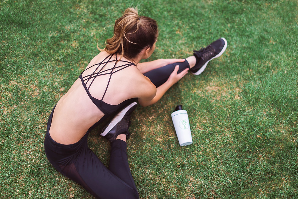 Young Fit brunette woman in a sports bra and leggings, on the ground stretching in the grass.