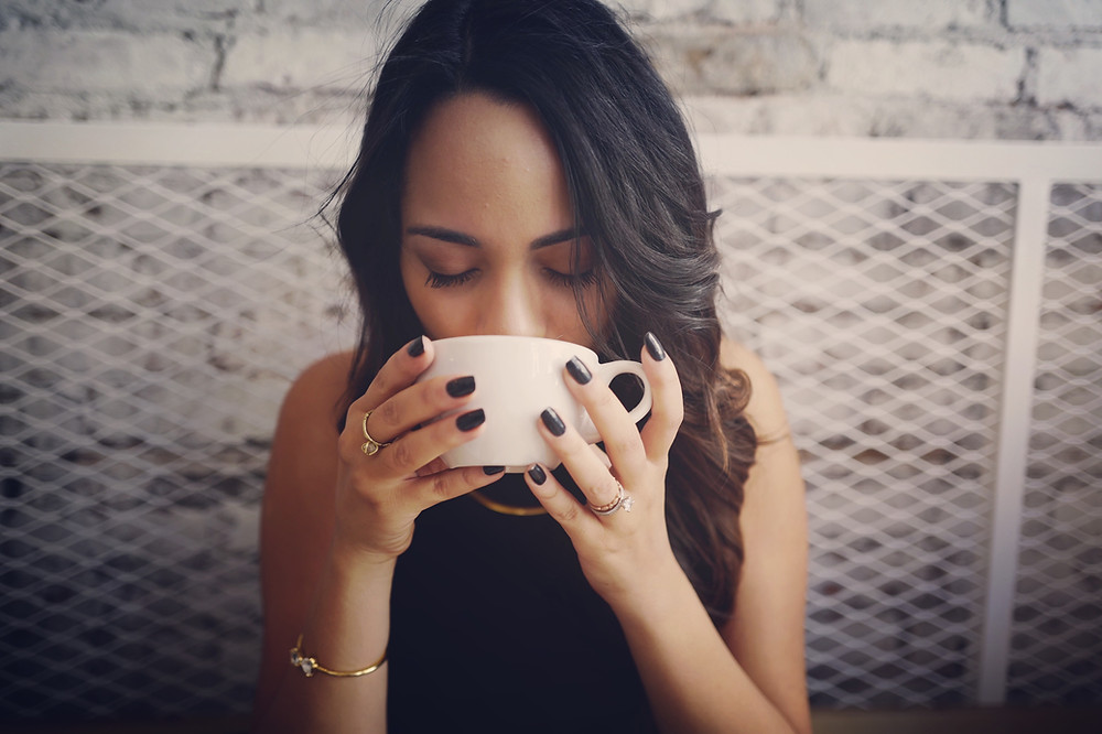 A woman sipping coffee from a coffee cup