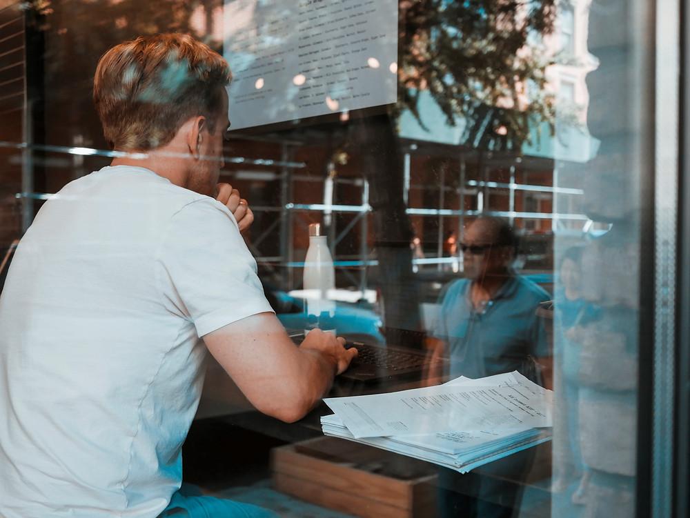 Man sitting working on laptop waiting for FAC3UK cv