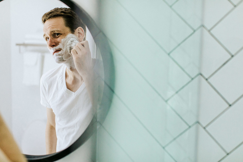 white man shaving and looking in mirror making foam with brush