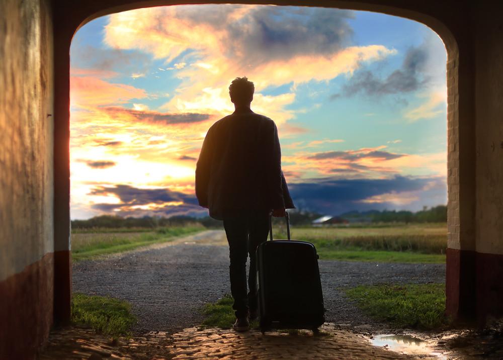 Mann geht mit Koffer aus der Dunkelheit in den Sonnenaufgang.