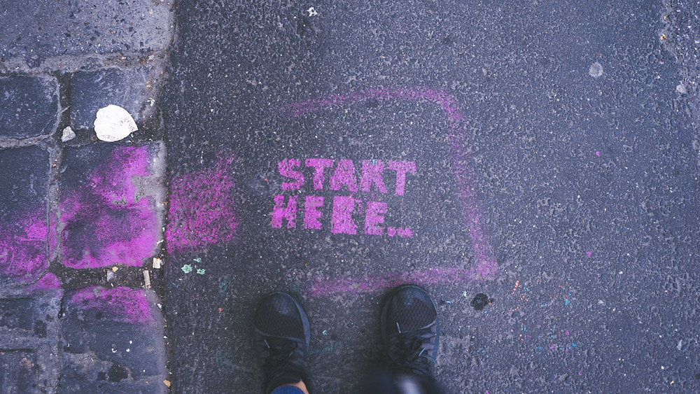 "The words ""start here"" on the asphalt"