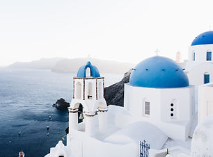 Pristine white building and blue dome rooftops of Santorini, Greece. Plan my trip to Greece
