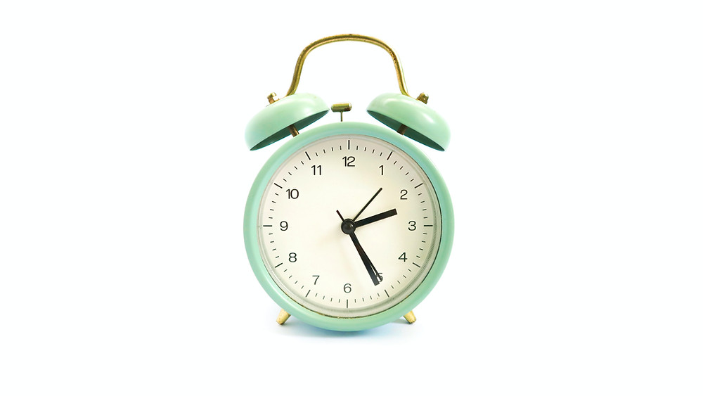 Old fashioned green alarm clock with the time 2:26 on it.