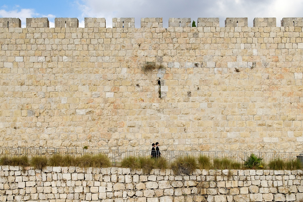 2 Jewish men walking along a road next to the walls of the Old City of Jerusalem