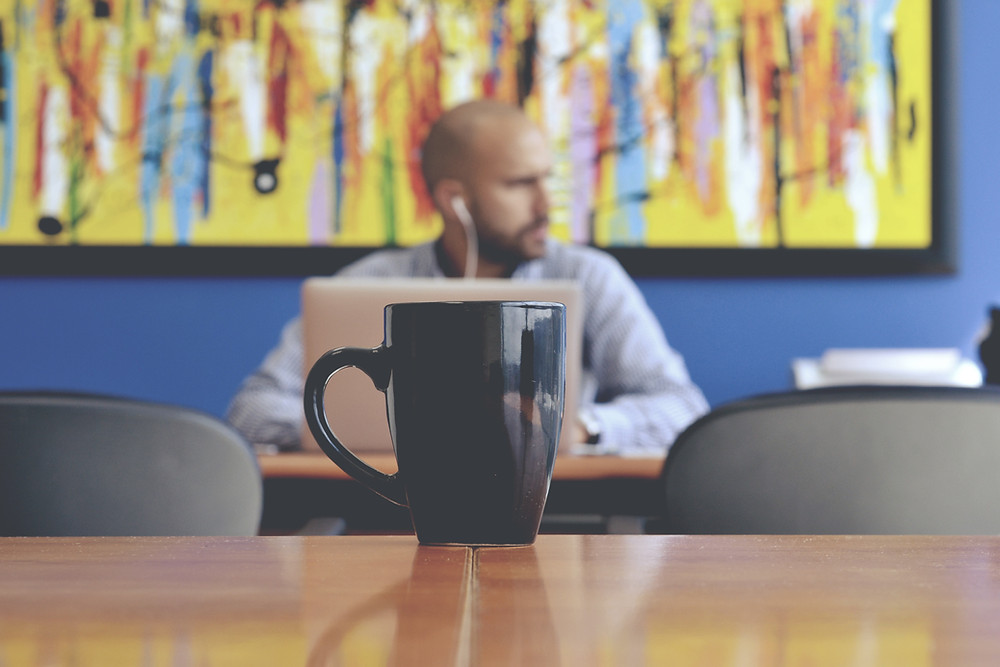 A coffee mug on an office table, with an office worker in the background