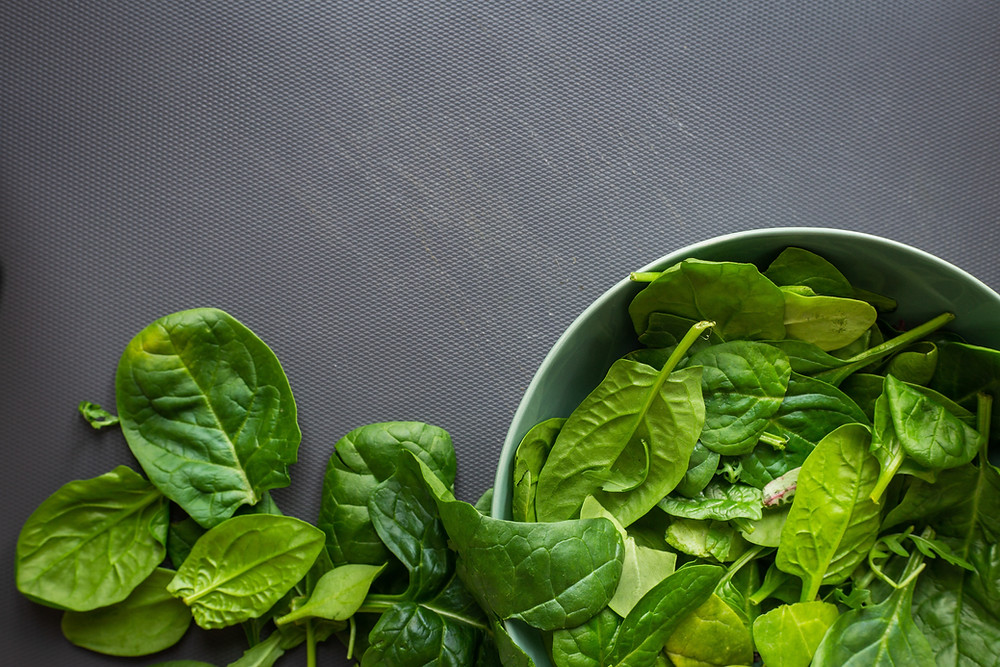 Spinach in a bowl on a cutting board
