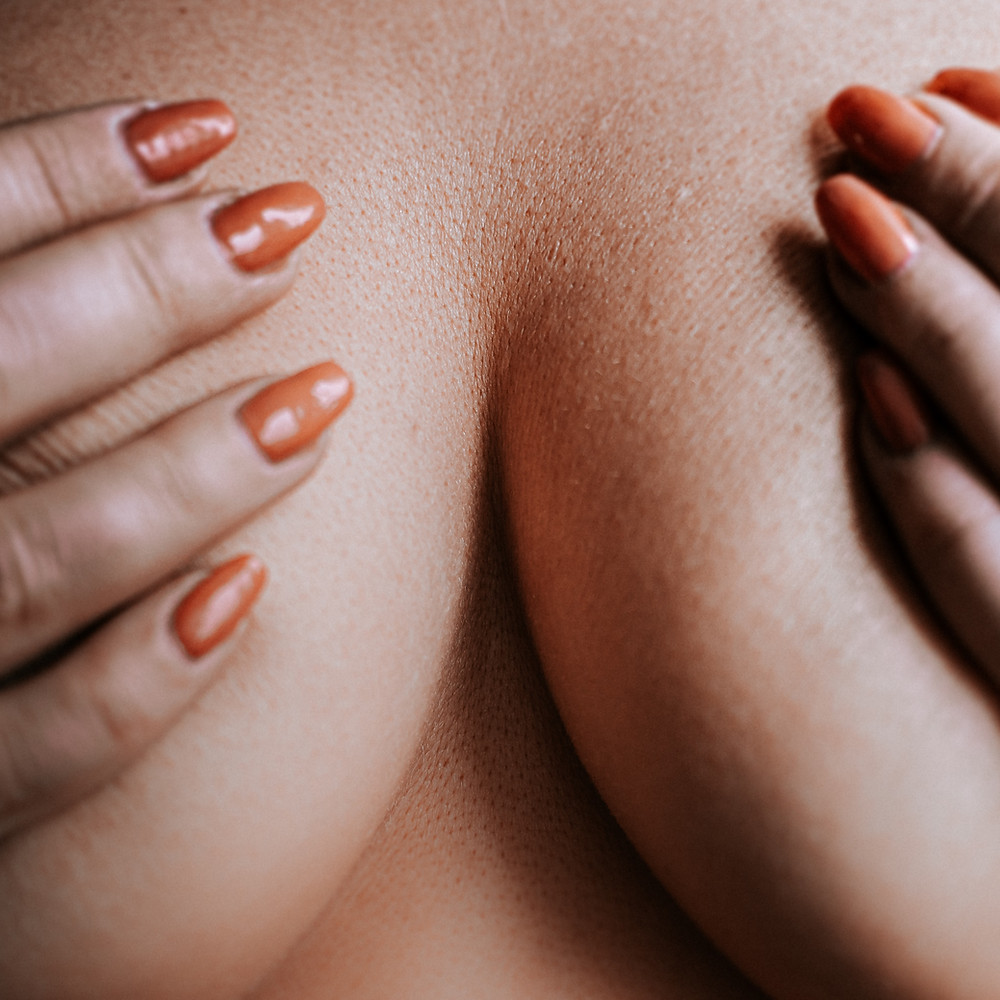 Breast with manicured hands covering the nipples