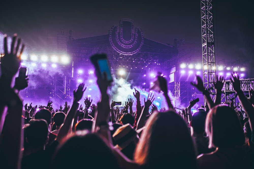 A Music Festival. Looking towards the stage through a sea of arms waving and holding cameras. The images has a purple hue and the Dry ice smoke from the stage area is casting the hue across the picture