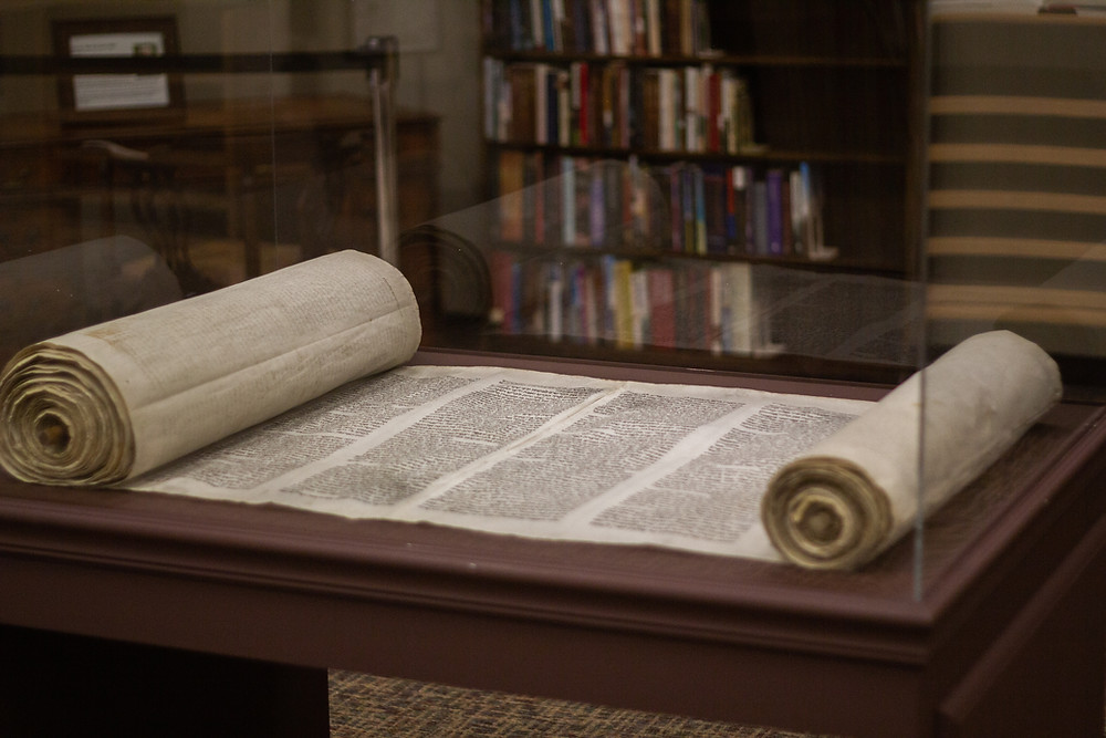 Torah open on a table, with a bookshelf in the background.