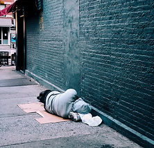 Homeless person sleeping on a bed of cardboard on an empty street