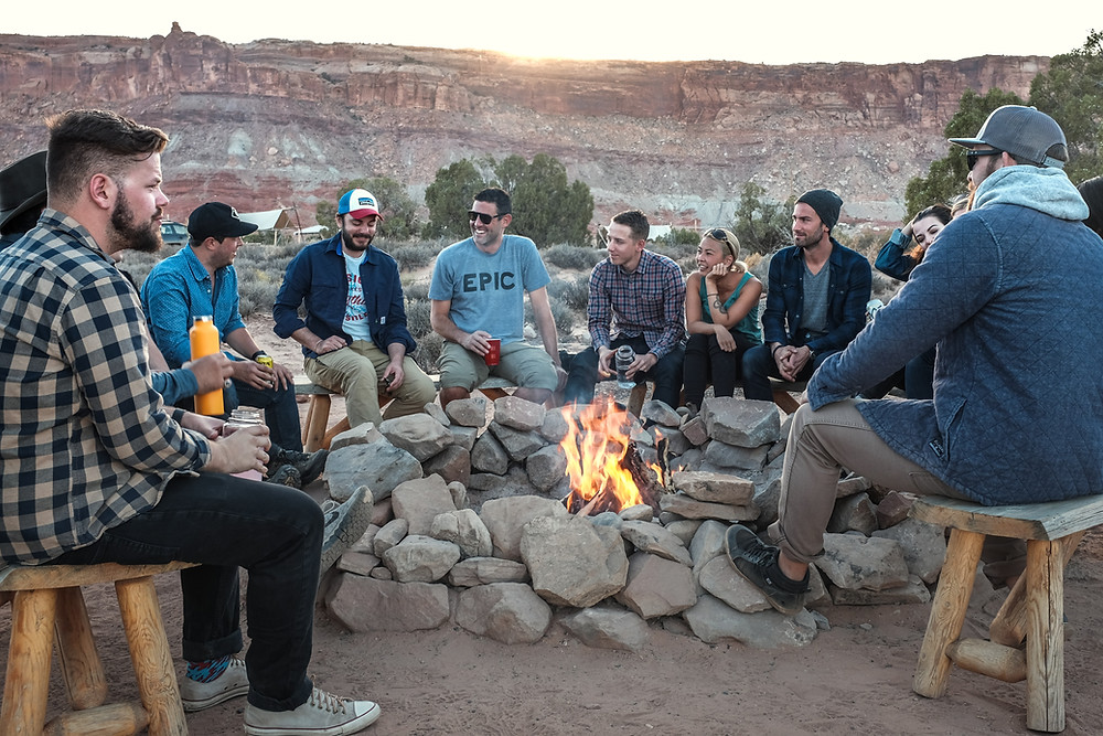 Men and women sitting around a campfire with a ring of rocks around it in a canyon with some trees at sunset.