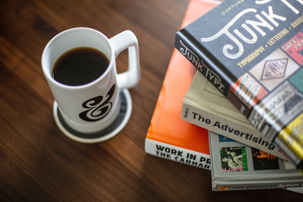 A cup of black coffee beside a pile of books on creativity