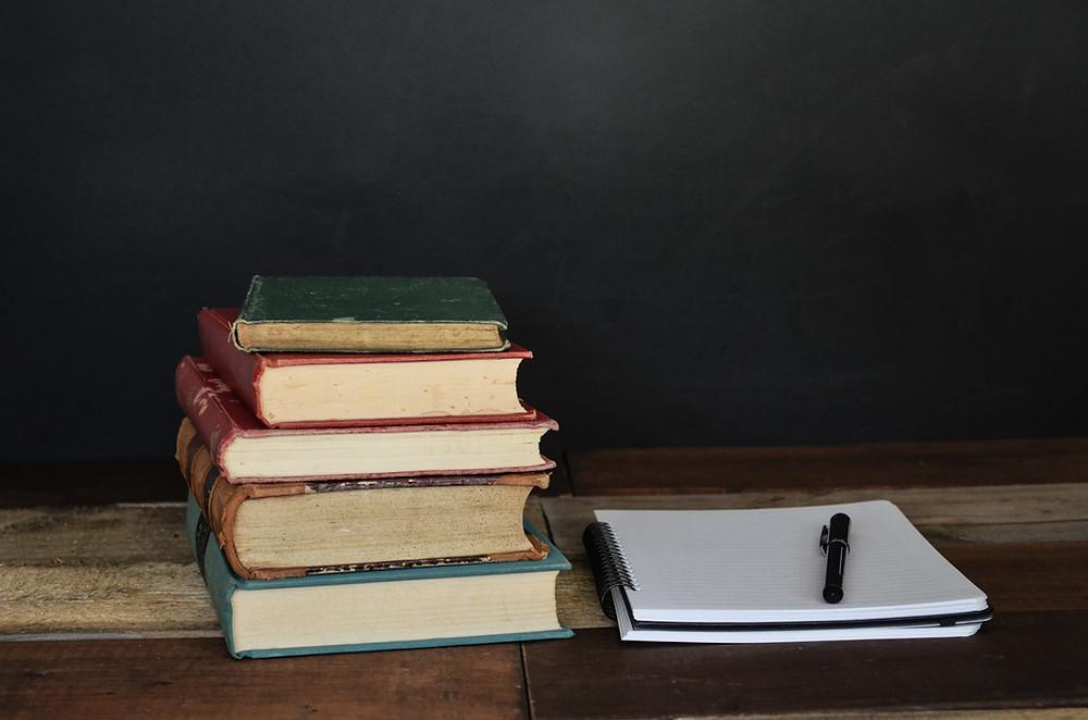 กองหนังสือเรียนพร้อมสมุดกับปากกาด้านข้าง