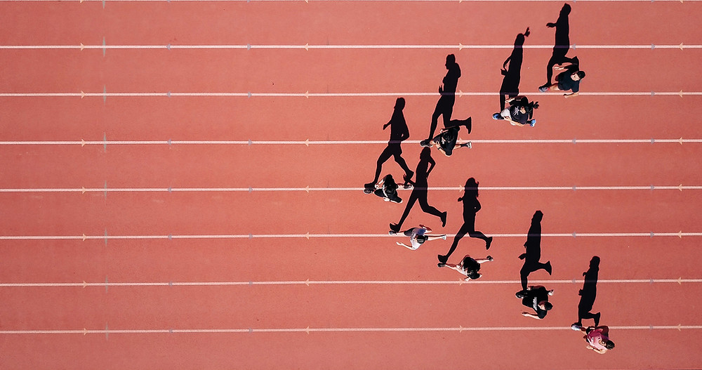 Interesting overhead shot of school track team running on track while shadows show arrow shape.