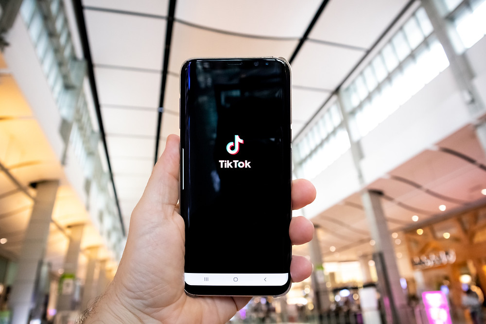 """A hand holding up a screen with the TikTok app open. """"Super Straight"""" appears to have originated from TikTok. Photo by: Olivier Bergeron/Unsplash."""