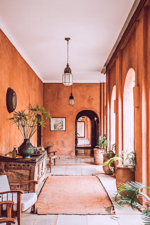 Loggia en enfilade qui laisse pénétrer la lumière par des baies en hauteur. La couleur des murs terracotta apporte une ambiance méditerranéenne et authentique.
