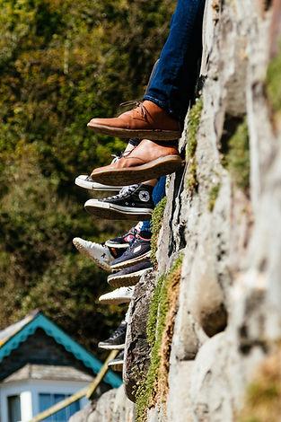 Shoe-shod feet of people sitting on wall