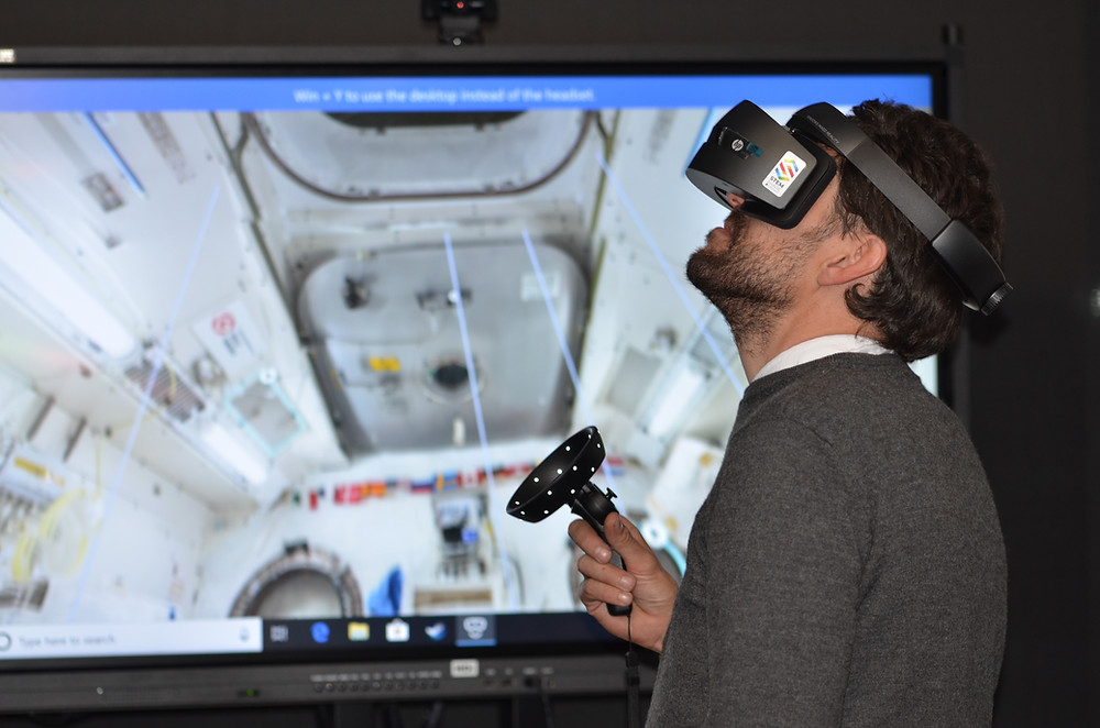Man with VR headset looking up while holding a VR controller, A space station can be seen on the background.