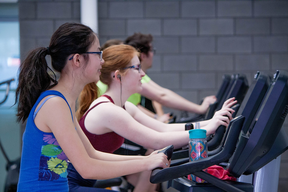 women at a gym riding stationary bikes