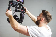 Videographer in White Shirt Using a Camera Gimbal Stabilizer