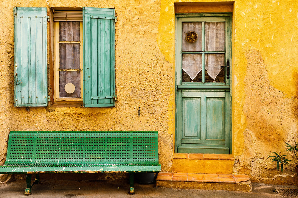 an ochre colored house with faded green shutters in Roussillon